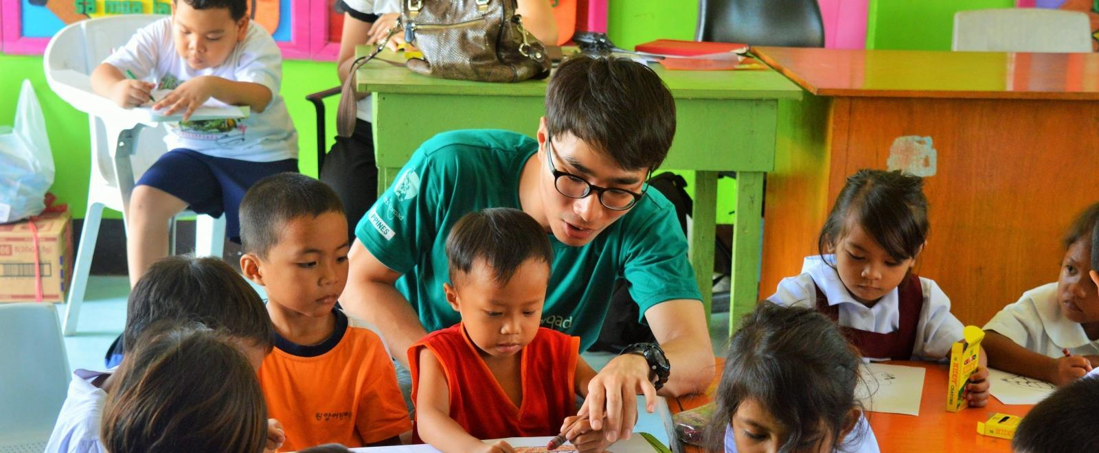 Students colour in a worksheet while learning about dental hygiene from a Projects Abroad volunteer teaching in the Philippines.